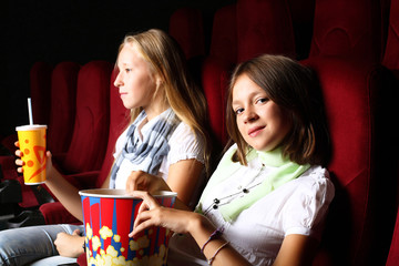 Two young girls watching in cinema