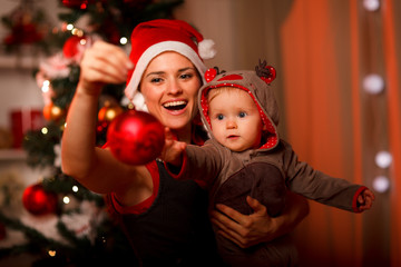 Mother showing Christmas ball  to baby near Christmas tree