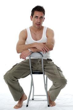 Homme en débardeur assis sur un tabouret