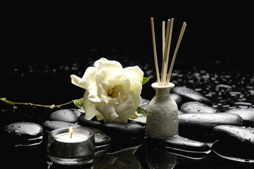 bottle of aromatherapy oil and candle with camellia on pebble