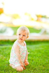 Thoughtful baby playing on grass