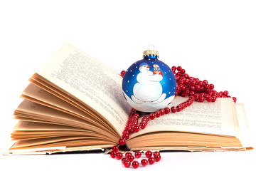 Blue christmas ball  with red pearls on a book