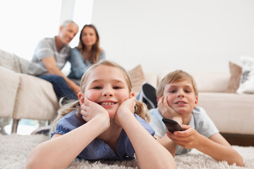 Siblings watching television with their parents on the backgroun