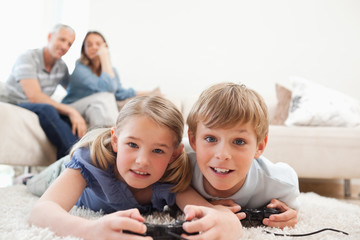 Playful children playing video games with their parents on the b