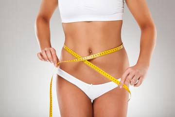 Woman measuring her slim body