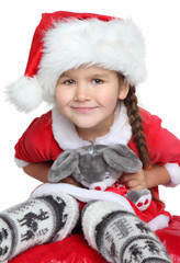 Portrait of happy little girl with toy in santa claus clothes