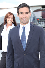 Businessman standing with a woman and light aircraft