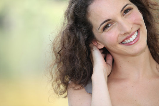 Closeup head and shoulders of a relaxed summery woman outdoors
