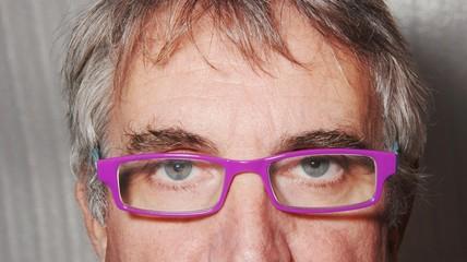 particolare di volto maschile con occhiali