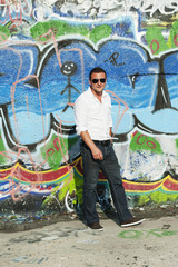 young man sitting in front of a colorful graffiti wall.