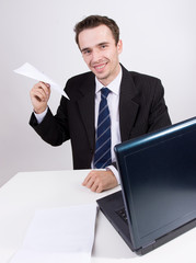 Businesman in office, paper airplane, smile, laptop