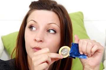 young woman with a condom (focus on face)