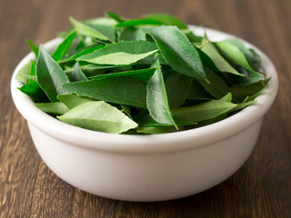 close up of a bowl of fresh indian curry leaves