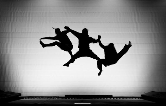 silhouette of friends jumping on trampoline
