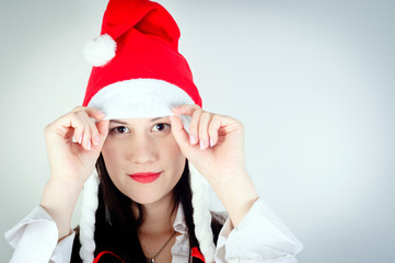 Girl in Santa's hat against white background