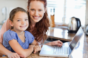 Mother and daughter with notebook in the kitchen