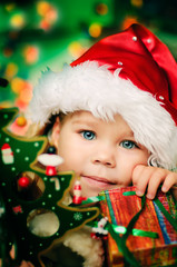 Happy small girl in santa hat with lot of gift have a christmas