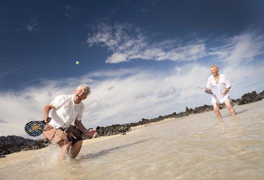 Active senior couple playing outdoor tennis