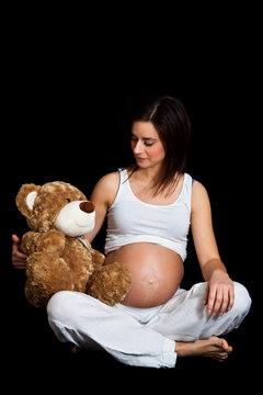 Brunette pregnant woman with teddy bear isolated on black