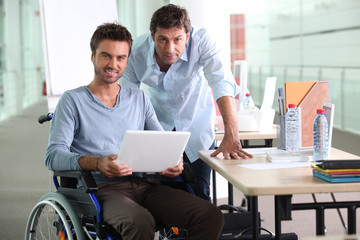 Man in wheelchair holding laptop computer next to colleague