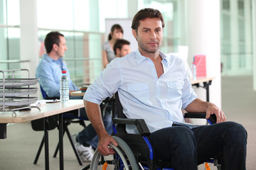 Man using a wheelchair in an office environment