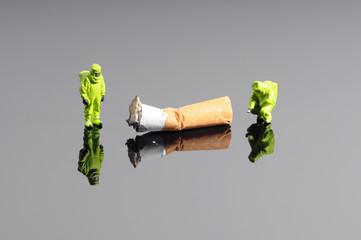 Tiny firefightes figures in hazmat suits examine cigarette butt