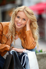 Trendy beautiful woman in town with shopping bags