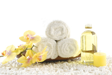 wooden bowl of towel and orchid with massage oil on white pebble
