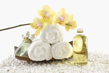 wooden bowl of towel and orchid with massage oil