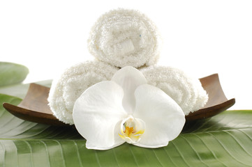 Wooden bowl of White orchid flower and towels on banana leaf