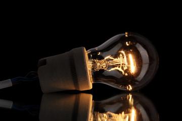 A lit light bulb on black background