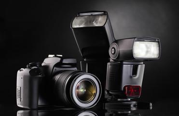 Black photocamera with flash on black background