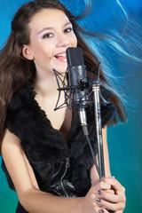 Junge Sängerin mit Mikrofon singt und hat Spaß