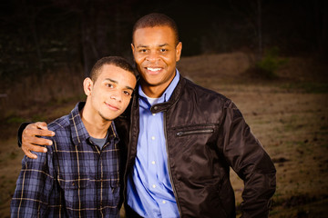 Portrait of African-American father and teenage son outdoors
