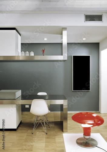 cucina hi-tech con piano di acciaio aperta sul soggiorno\