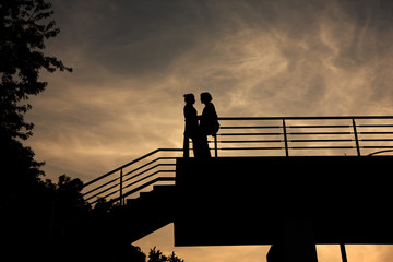 Silhouette of a couple in love on bridge