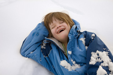 A girl with Down Syndrome laughing on snow