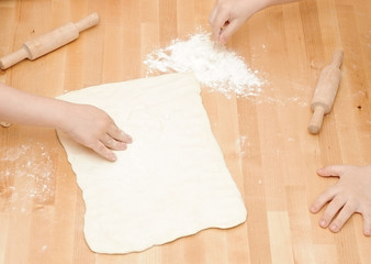 Child's hands kneading dough on wooden table