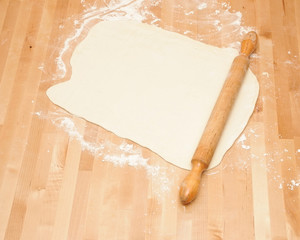 Classic wooden rolling pin with freshly prepared dough and dusti