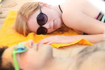 A couple of teenagers sleeping on the beach.