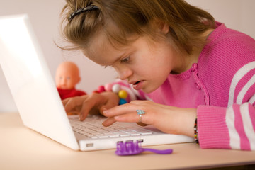 A girl with Down syndrome using a laptop.