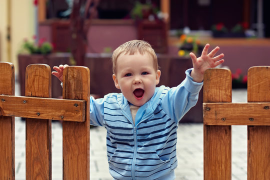 Cute boy standing in open wooden fence with welcome expression