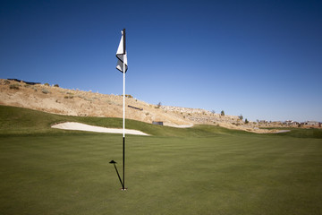 Golf course with green grass and clear blue skies.