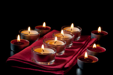 Tea light candles burning in the darkness