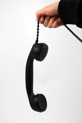 Hand hält sehr alten Telefonhörer an Strippe