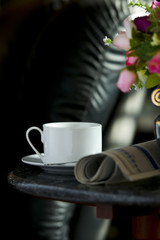 Coffee cup with flower and newspaper