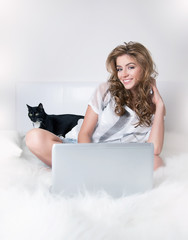 Smiling young girl in white bed with black cat and laptop
