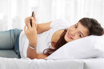 woman texting on phone while lying on bed