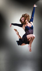stylish and young modern style dancer jumping in studio