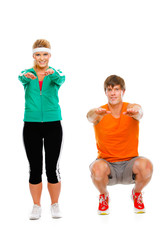 Portrait of girl and man in sportswear sitting on squat